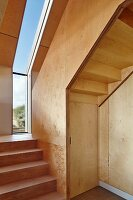 Camber Sands Beach Houses, Rye, United Kingdom. Architect: Walker and Martin, 2014; Plywood staircase with narrow window looking out over dunes