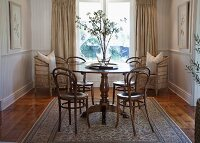 Thonet coffee-house chairs at round table in traditional-style living room