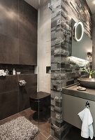 A toilet next to a dark tiled wall with a built in shelf and a glass partition with a limestone relief wall next to the wash basin