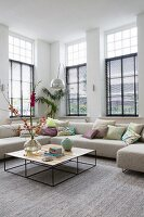 Coffee table with delicate metal frame in front of corner sofa in high-ceilinged living room with lattice windows
