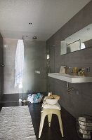 Designer bathroom in shades of grey with retro metal stool and shower area with glass screen