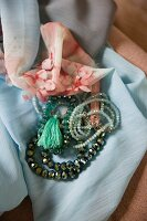 Nostalgic arrangement of various beaded necklaces on pastel blue scarf