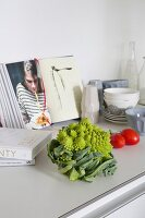 Romanesco cauliflower and tomatoes in front of open cookery book on kitchen counter