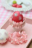 Red-dyed egg with floral motifs and pink trim in egg cup