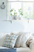 Sofa with scatter cushions in various shades of cream below window in wall painted pastel blue