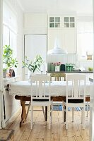 White kitchen chairs around table with tablecloth below pendant lamp with white metal lampshade in rustic dining room