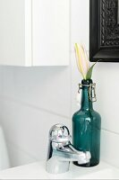 Flower in vintage, swing-top bottle next to tap fitting