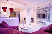 Open-plan, elegant, white living area with purple accents, atmospheric, indirect lighting and pendant lamps above kitchen counter