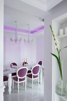 Dining table and crystal chandelier in dining room with purple, indirect lighting on ceiling and Neo-Baroque, upholstered chairs