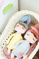 Fabric dolls with sleeping eyes and wearing bunny ears in wicker basket