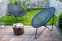 Modern outdoor easy chairs with grey string seats in small, fenced garden