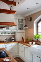 Kitchen counter with wooden worksurface and white, country-house-style base and wall units
