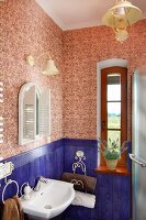 Corner of vintage bathroom with blue-painted wainscoting, patterned wallpaper, paraffin-style lamp and narrow window