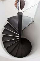 Spiral staircase with black wooden treads in white cylindrical stairwell