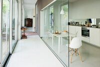 Narrow corridor with glass wall, dining set with classic, white chairs and modern kitchen counter