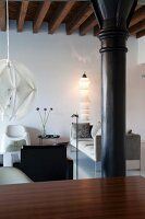 Lounge furniture and standard lamp in renovated loft apartment with black, industrial pillar and rustic, wood-beamed ceiling