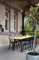 Wooden table and bistro chairs next to restored brick façade of loft apartment
