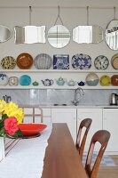 View across dining table; decorative plates on white shelves and collection of mirrors on wall above kitchen counter