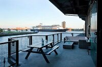 Spacious balcony with combination of outdoor furniture and view of cruise ship on river