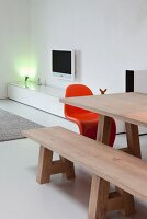 Wooden dining table and matching bench; spotlight on low, white sideboard in background