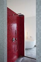 Shower area with red mosaic tiles; view of bathtub through open doorway