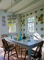 Wooden chairs around painted table in rustic dining room with white wooden ceiling
