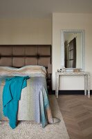 Console table below mirror next to bed with tall, brown, upholstered headboard and bedspread with subtle gradient of colours