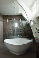 Free-standing, spa bathtub in front of shower area with glass sliding doors