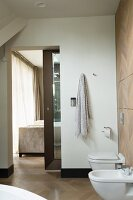 Bathroom with bidet, wall-mounted toilet and view into bedroom through open sliding door