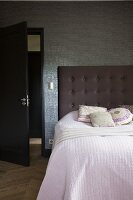 Bedspread on bed with tall, button-tufted headboard against wallpapered wall
