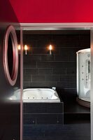 Black-tiled, futuristic bathroom with whirlpool and modern shower cubicle; view through open door with porthole