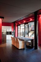 Dining area and kitchen in open-plan interior with glass wall framed in red