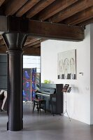 Black metal pillar under wooden beam structure with piano, bench and music stand in background