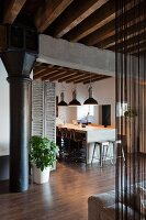 Industrial charm in loft apartment with black metal column under concrete girder and wood-beamed ceiling; modern dining area with row of pendant lamps in background