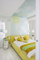 View through open door of double bed with white and yellow bed linen and stripe of floral wallpaper on wall and ceiling