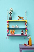 Colourful, hand-made shelves with wooden beads threaded on climbing ropes and decorated with vintage-style toys