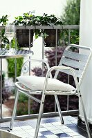 Stainless steel outdoor chairs with white cushion next to bistro table on balcony