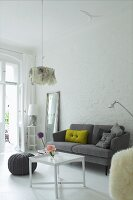 Scatter cushions on grey, retro sofa against whitewashed brick wall in interior with traditional ambiance