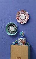 Old colander and steamer embroidered with colourful yarn and with small mirrors in centres decorating wall