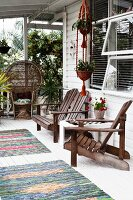 Wooden armchair, bench and side table on terrace outside wooden house with colourful rug on white-painted wooden floor