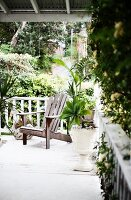 Wooden armchair on white-painted terrace in tropical garden