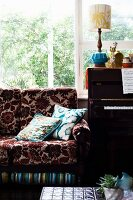 Floral sofa next to piano in front of window