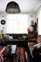 Dark leather couch and patterned sofa around coffee table on ethnic rug in rustic interior