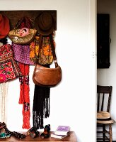 Hats and bags hung on coat rack next to open door with view of rustic wooden chair