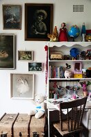 Knick-knacks and painting utensils on desk with shelves on top painted white next to pictures on wall