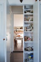 Kitchen utensils in cupboard built into doorway and open doors with view into dining room