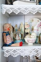 Doll, collectors' items and religious ornaments on shelf decorated with white lace trim