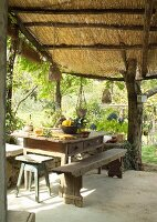 Rustic table with bench and stool below straw-thatched pergola in summer garden