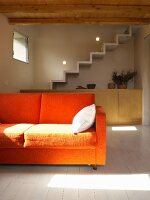 Orange sofa in sunshine; concrete staircase above sideboard custom-made in pale wood