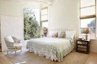 Bright bedroom with ruffled bedspread on double bed and open window with garden view